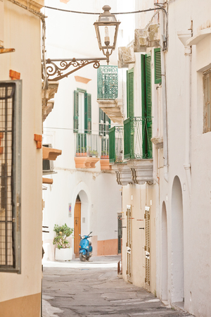 Gallipoli, Apulia, Italy - A traditional street lamp in a historical lane with a motor scooter Standard-Bild - 101525225