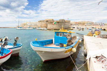 Gallipoli, Apulia, Italy - Fishing boat at the seaport in front of the town wall Standard-Bild - 101522889