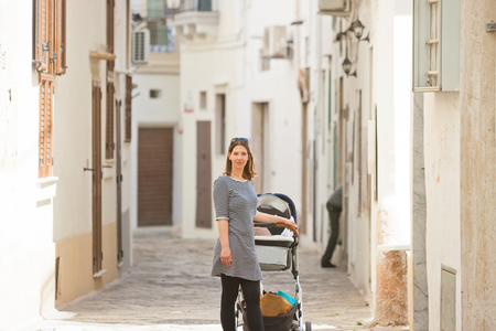 Gallipoli, Apulia, Italy - A woman with a stroller in a middle aged alleyway Standard-Bild - 101525228