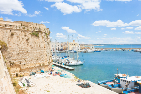 Gallipoli, Apulia, Italy - Sailing boats at the harbor near the historical city wall Standard-Bild - 101535363