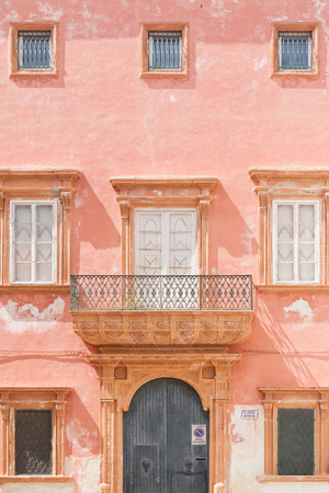 Gallipoli, Apulia, Italy - A pink facade with a barn door and several windows Standard-Bild - 101711372
