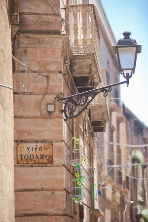 Taranto, Apulia, Italy - An old street lamp fixed at a house facade Editorial