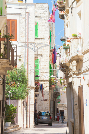 Molfetta, Apulia, Italy - JUNE 3, 2017 - Tourists walking through an alleyway in the old town of Molfetta