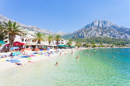 Gradac, Dalmatia, Croatia, Europe - AUGUST 24, 2017 - Several tourists bathing and relaxing at the beach of Gradac