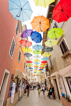 Novigrad, Istria, Croatia, Europe - SEPTEMBER 3, 2017 - Tourists walking through the old town of Novigrad with umbrellas above them Editorial