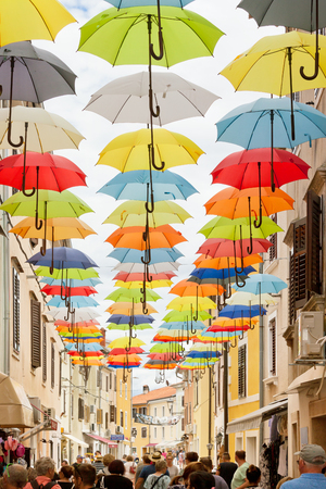 Novigrad, Istria, Croatia, Europe - SEPTEMBER 3, 2017 - Tourists walking through an alleyway with colorful umbrellas above Editorial