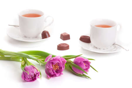 Pink tulips with cups of tea and chocolates isolated photo