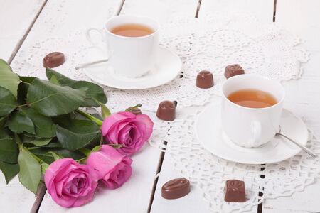 Pink roses tulips with cups of tea and chocolates photo