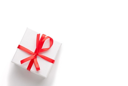 goodie: White gift box with red ribbon and bow, isolated.