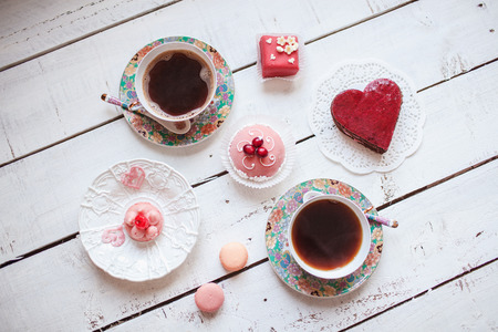english food: Delicious red heart cake with several cakes and two cups of coffee