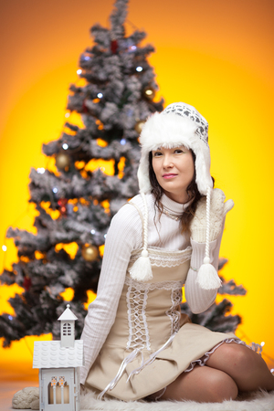 Beautiful Japanese girl with gifts in decorated Christmas tree, studio shot, studio shotting, for cover, text place Stock Photo