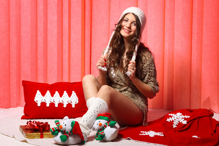 wearing slippers: Pretty tenager girl with long hair wearing knitted hat and christmass slippers