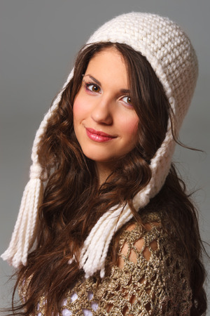 Pretty young woman with long hair wearing a crochet hat and cape