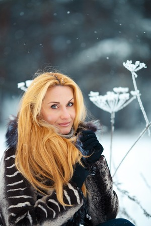 beautiful woman with long red hair on a snowy Cow Parsnip.