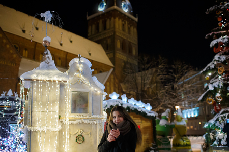 cinematic: Long hair girl on European Christmas Market. Young woman Enjoying Winter Holiday Season. Blurred Christmas Lights background, dusk. Cups with drink in hand. Selective focus