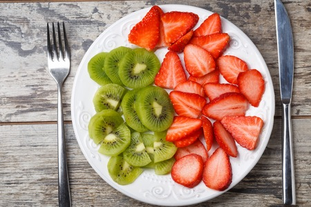 fresh strawberry and kiwi slices on cutting plate with fork, knife. Stock Photo