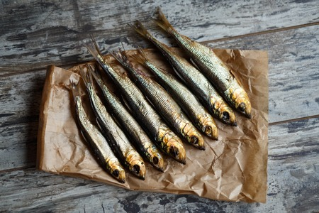 smoked herring on a paper and wooden table.