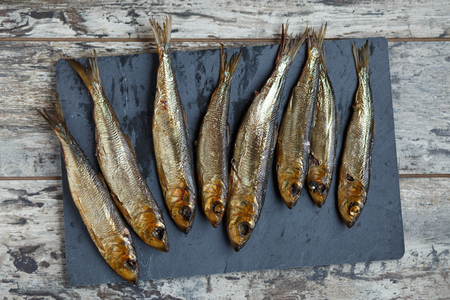 smoked herring on a wooden table and slate board. Stock Photo