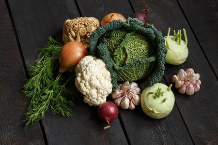 Spring vegetables on a dark background: Savoy cabbage, cauliflower, onion, garlic, kohlrabi, celery root, dill