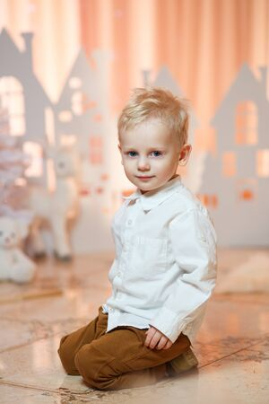 Cute blonde hair little boy near christmas toy paper houses Stock Photo