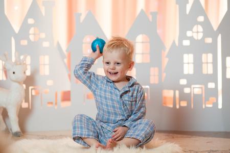 Cute blonde hair little boy in sleepwear near christmas toy paper houses