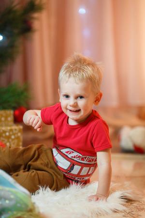 Cute blonde hair little boy keeps a gift. Imagens