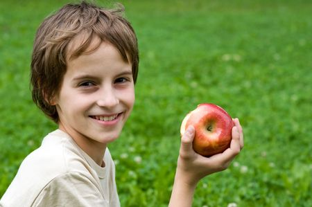 preteen boy: Portrait of a preteen boy with a apple in his hand and green grass in the background