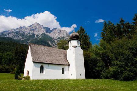 Small white church underneath the alpine peaks photo