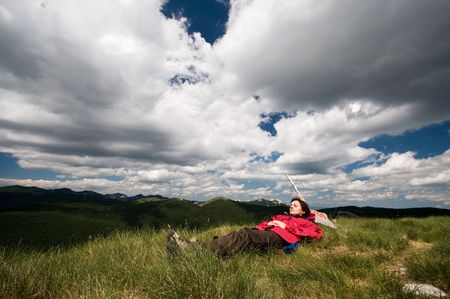 mountain peek: Woman is laying down on the grass on top of mountain peek, relaxing from everydays troubles with dramatic clouds over her head Stock Photo