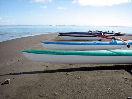 dugout: Aligned Polynesian dugout Stock Photo