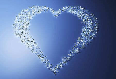 a group of many small diamonds have been put together to form a shape that represents a heart that is lying on a blue background, and a light over its left side illuminates the scene Stock Photo