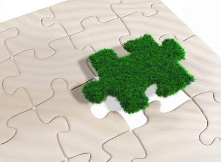 art piece: a last missing puzzle piece made of grass is going to be inserted in a puzzle made of sand Stock Photo