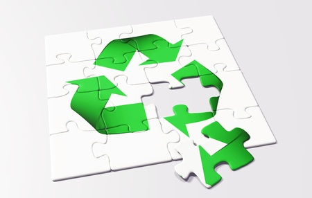 a last missing puzzle piece is lying on a puzzle where it is shown a green recycling symbol on a white background Stock Photo