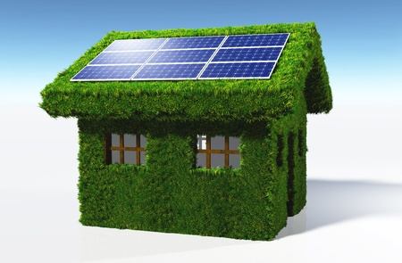reflects: a small house covered by grass on the walls and on the roof, has some solar panels placed on one side of the roof with the sun that reflects in them, on a white background and a blue sky Stock Photo