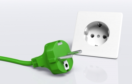 disconnected: ecological european disconnected green plug lies on the ground in front of a white socket Stock Photo