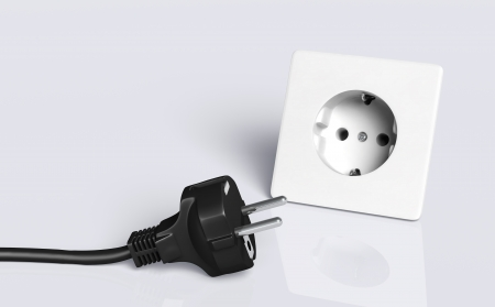 disconnected: european disconnected black plug lies on the ground in front of a white socket Stock Photo