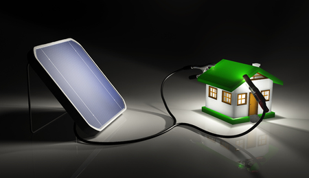 a squared solar panel illuminated by a light is supplying energy to a small house with two terminals connected on the roof  On a dark background Stock Photo