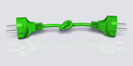 two ecological green plugs are connected by one green knotted cable on a white background Stock Photo