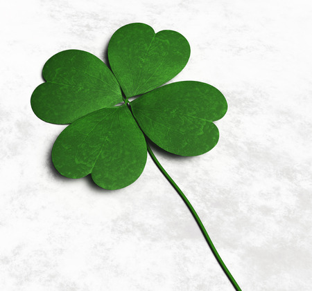 a green four-leaf clover is lying on a white and grey abstract ground
