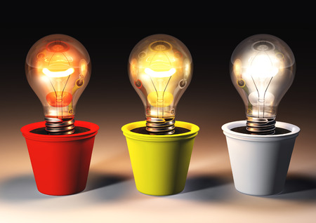 three lit light bulbs with different light color are growing in colored pots that lie on a dark background Stock Photo