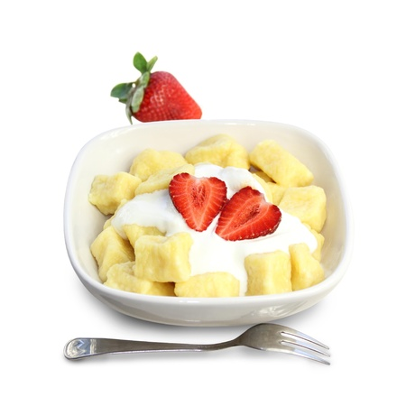 Sweet cottage cheese gnocchi with sour cream and strawberries. Isolated on white background.