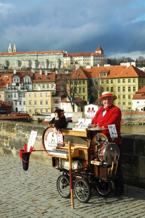 Charles Bridge in Prague, Czech Republic. A man offers music from hand operated music box in exchange for money.