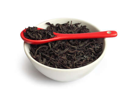 Dry black leaf tea in a bowl with red spoon photo