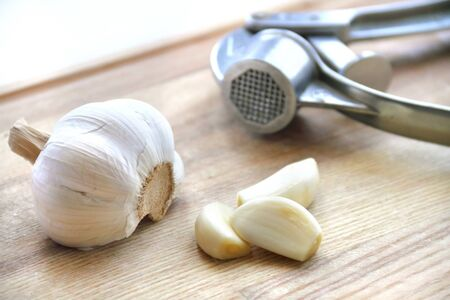 Garlic and garlic press on wooden cutting board photo