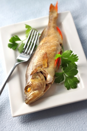 River perch baked in foil with parsley Stock Photo