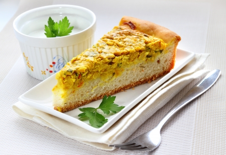Piece of tart with onions, cheese and turmeric Stock Photo