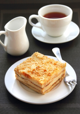 Piece of Napoleon cake with cup of tea photo