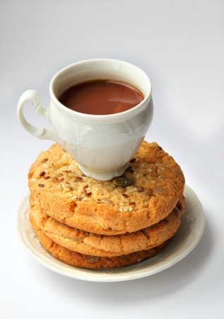 Sweet cookies with different kinds of seeds and cup of hot chocolate photo