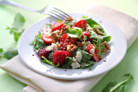 Salad with arugula, strawberries, goat cheese and walnuts dressed with balsamic vinegar and olive oil