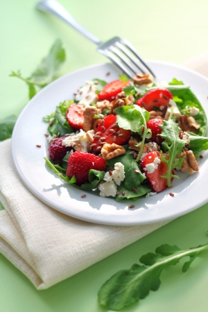 Salad with arugula, strawberries, goat cheese and walnuts dressed with balsamic vinegar and olive oil photo